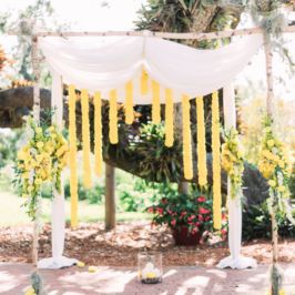 Outdoor wedding arch with yellow flowers and cascading design by Beneva Weddings Sarasota FL